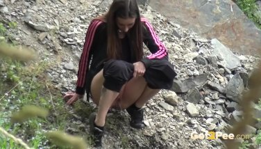 Desperate to pee brunette relieves herself