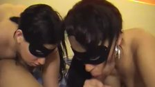 Masked brunettes sucking a black cock