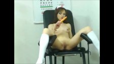 Hot brunette nurse plays with an orange dildo