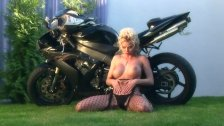 Busty blonde teases on a motorcycle in nylon