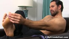 Handsome businessman shows off his feet