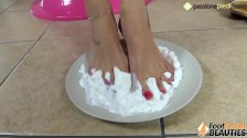 Barefoot brunette covers her feet in sweet cream