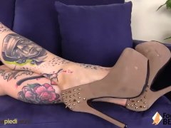 Barefoot tattoed girl massages her feet